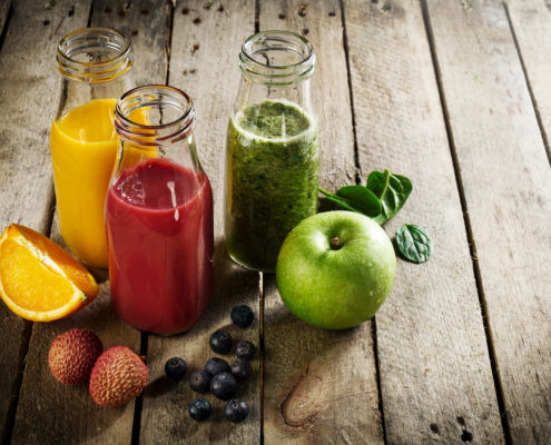 Tasty colorful fresh homemade smoothies in glass jars on wooden table. Healthy, detox concept.
